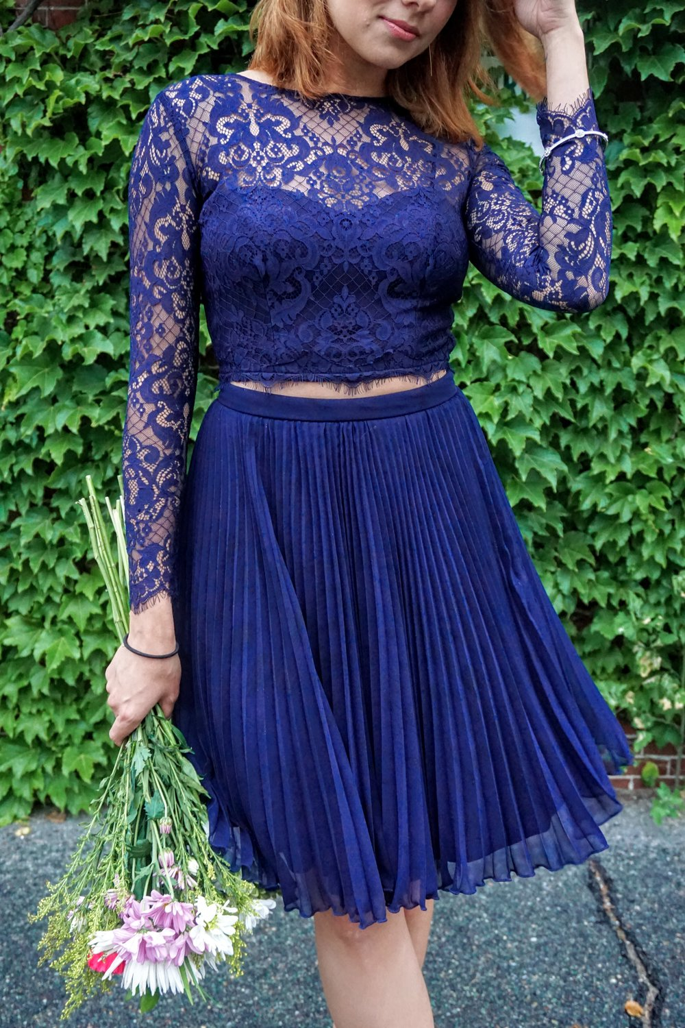 A close-up of an outfit: dark blue lace top and skirt.