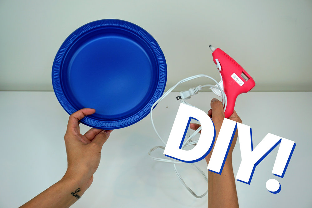 Blue plastic plate and pink glue gun for a DIY makeup brushes mat.