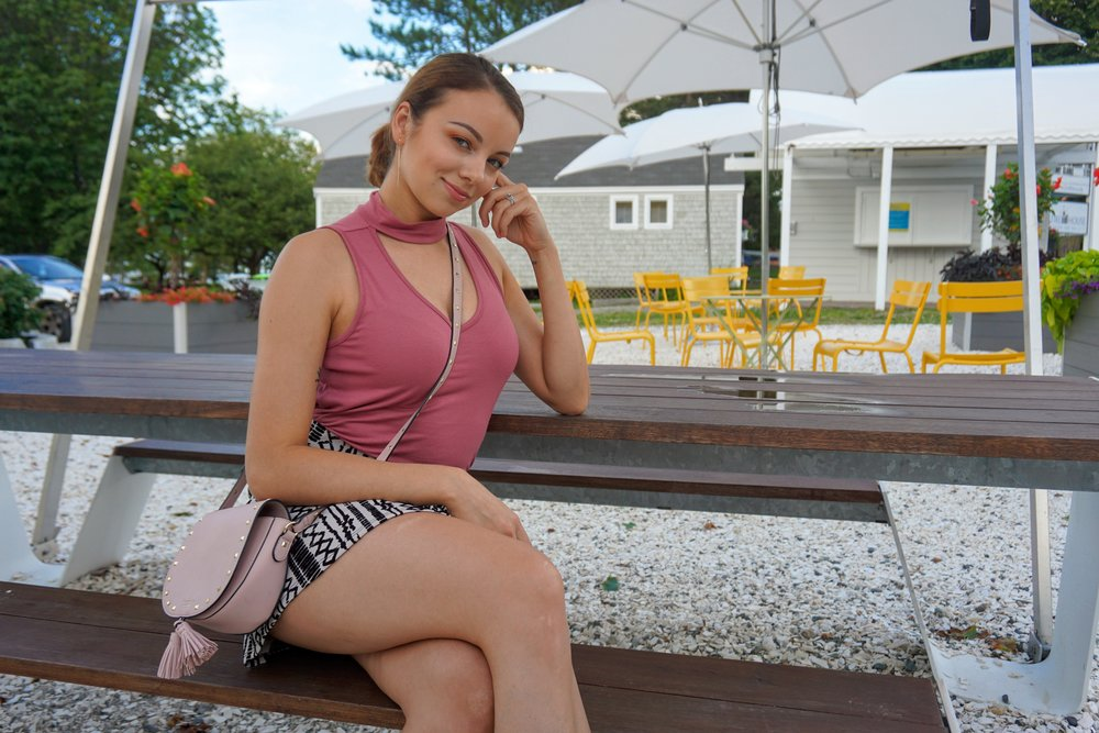 A girl sitting under the umbrella. She is wearing a pink choker top, black and nude patterned skirt, and a crossover bag.