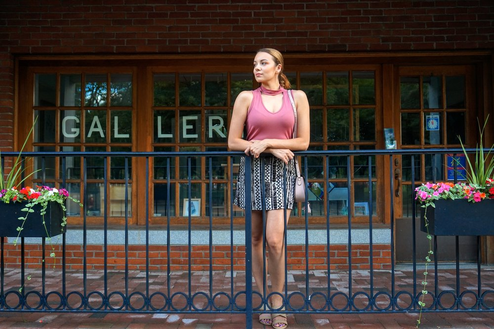 A girl standing near the gallery. She is wearing a pink choker top, nude and black patterned skirt, and a crossover pink bag.