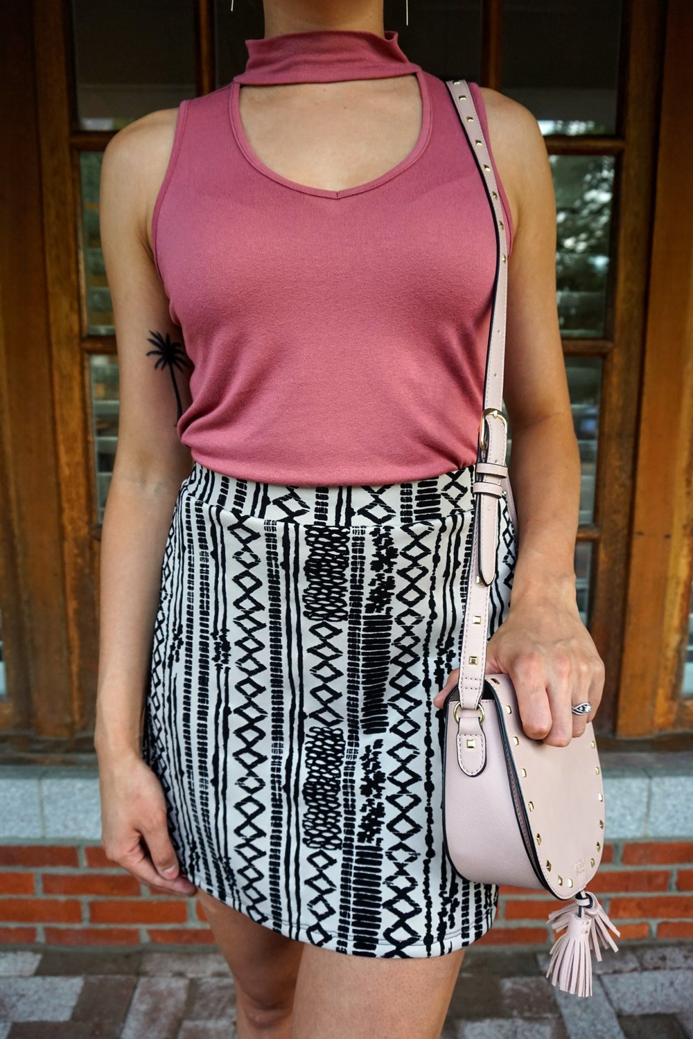 Details of a blogger's outfit: a nude and black patterned skirt, pink choker top tucked into the skirt, and a pink crossover bag.