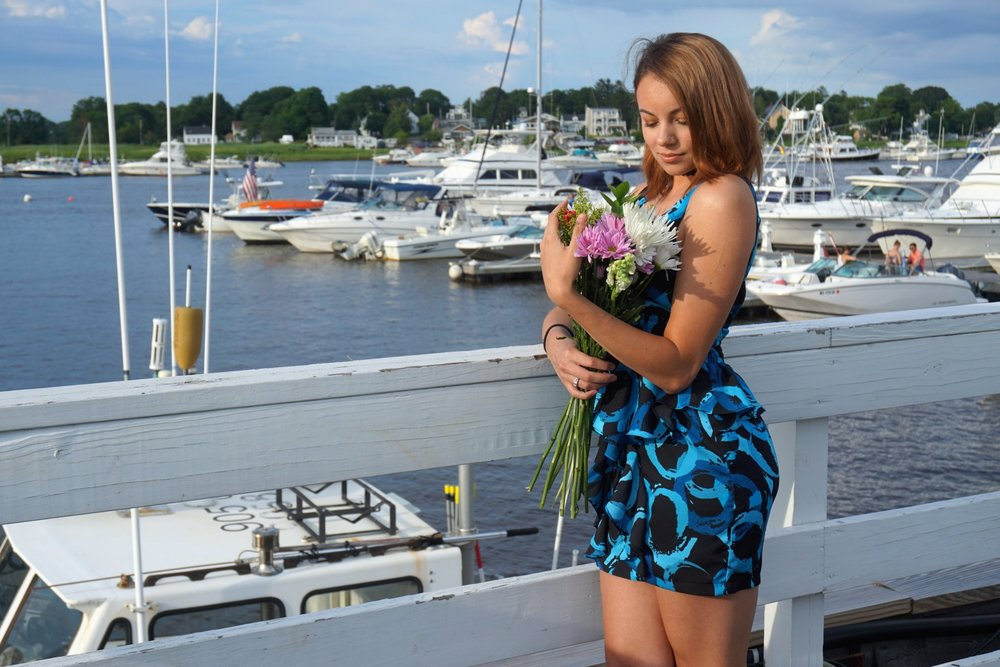 A girl holding flowers by the pier.