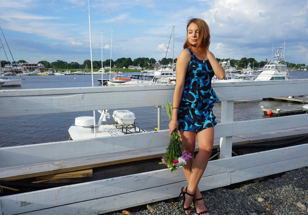 A girl standing on the pier, holding flowers, and wearing a blue raffled dress with high heeled sandals.