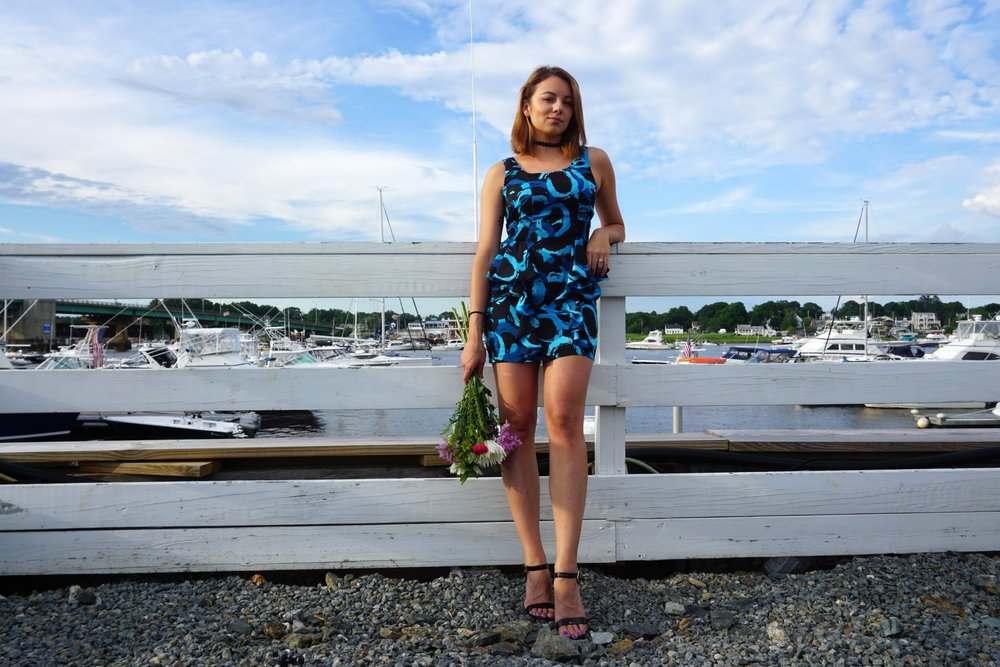 Blogger on the pier, holding flowers, wearing a blue sleeveless dress and black high heeled sandals.