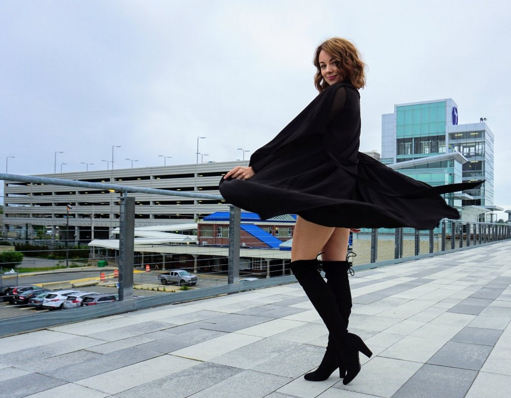 A girl swirling a black duster that she is wearing.