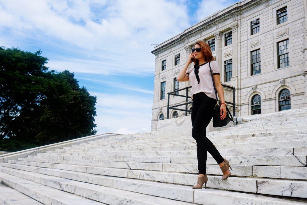 A blogger walking down the stair shot. She is wearing a business casual outfit.