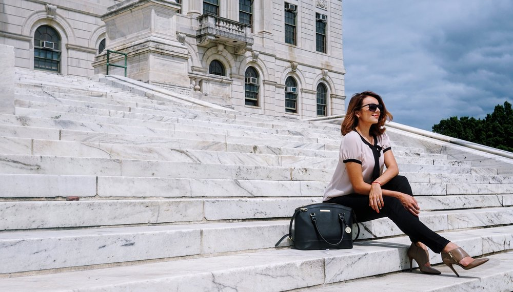 A blogger sitting on the stair, wearing a business casual outfit.