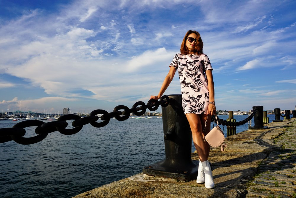 A beauty blogger posing by the Boston river, wearing a pink dress with black pattern, white boots, and light pink purse.