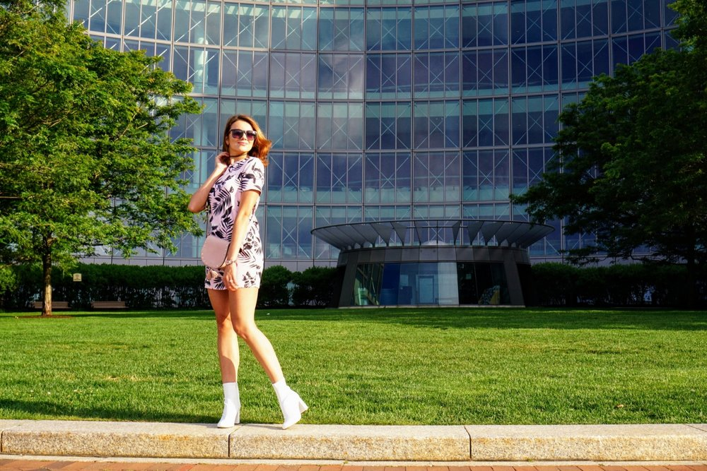 A blogger standing near a pretty Boston building, wearing a pink short dress, white boots, and a pink purse.