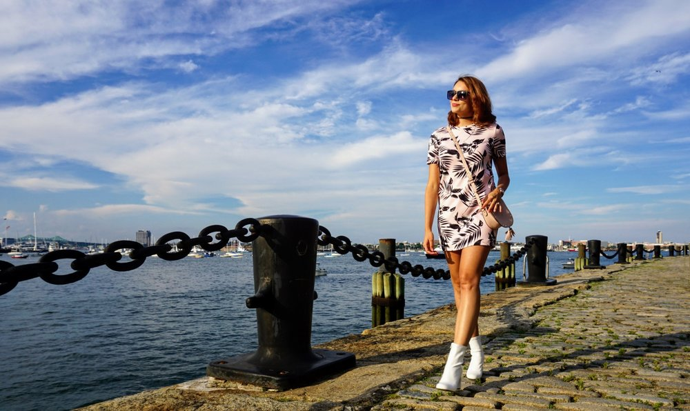 A fashion blogger walking by the Boston river, wearing a short pink dress, white over-the-ankle boots, black sunglasses, and pink purse.