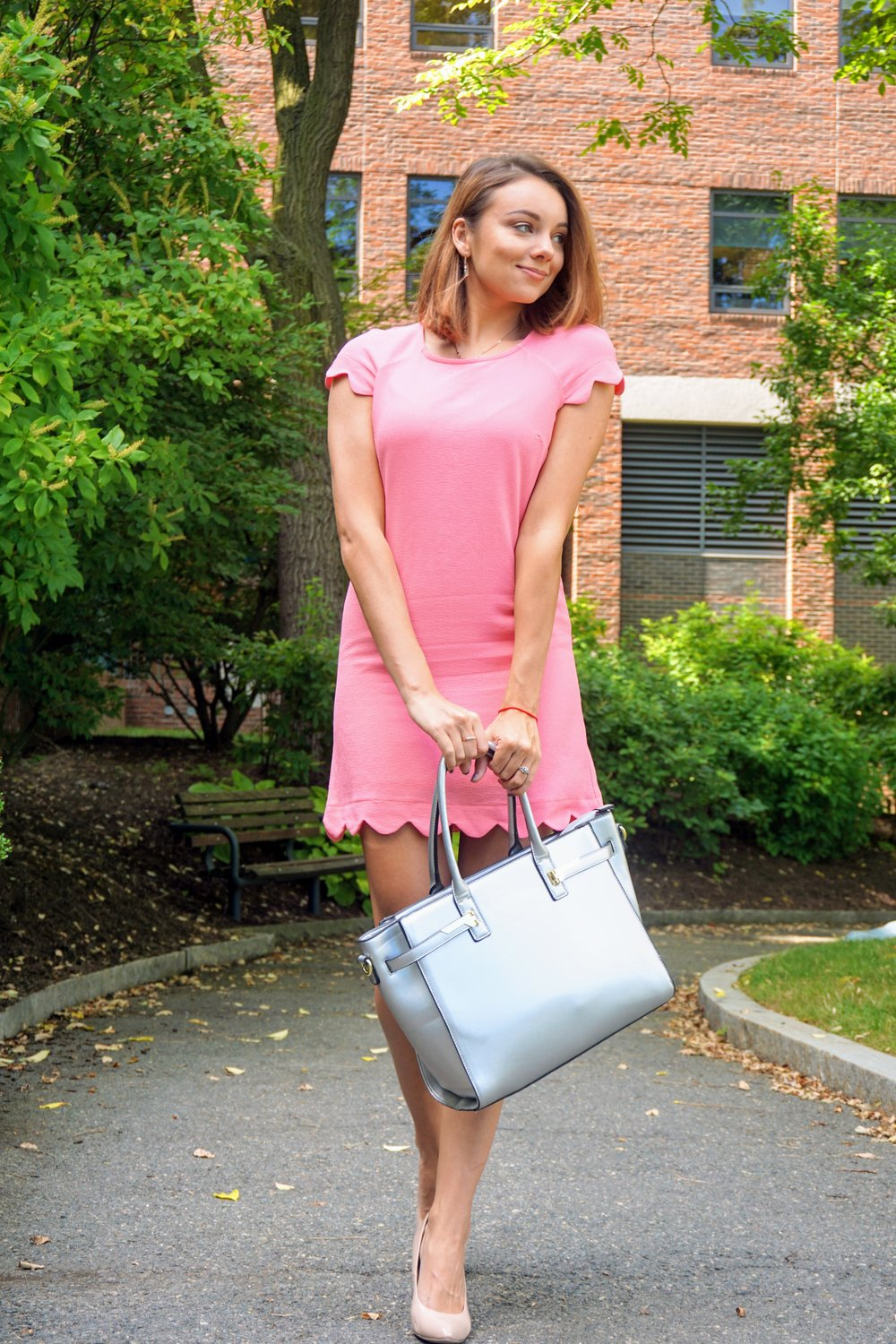 Fashion blogger posing in Boston, wearing a bubblegum pink dress, nude pumps, and a metallic silver bag.