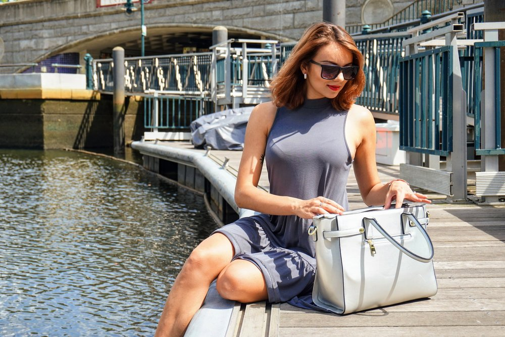 Blogger sitting on a pier, opening her silver bag.