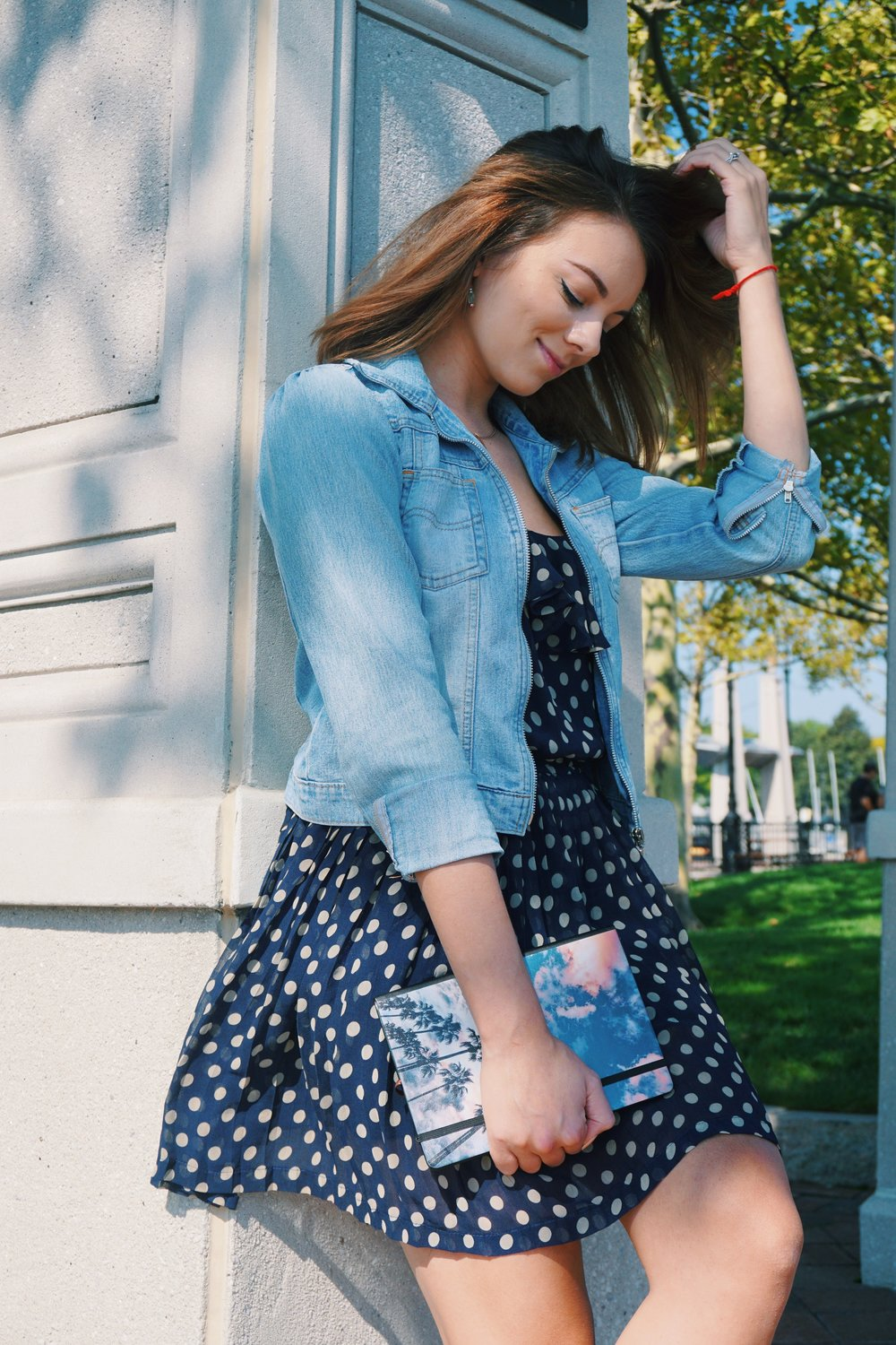 A beauty blogger standing in the park, wearing a summer polka dot dress, and a washed out denim jacket.