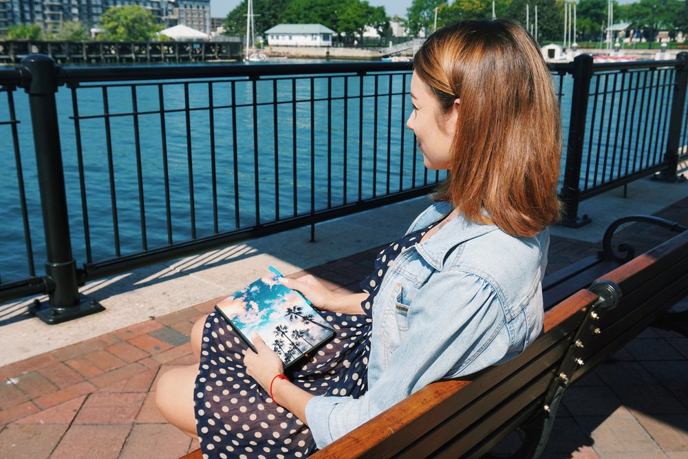 A blogger sitting on a bench, looking at the water.