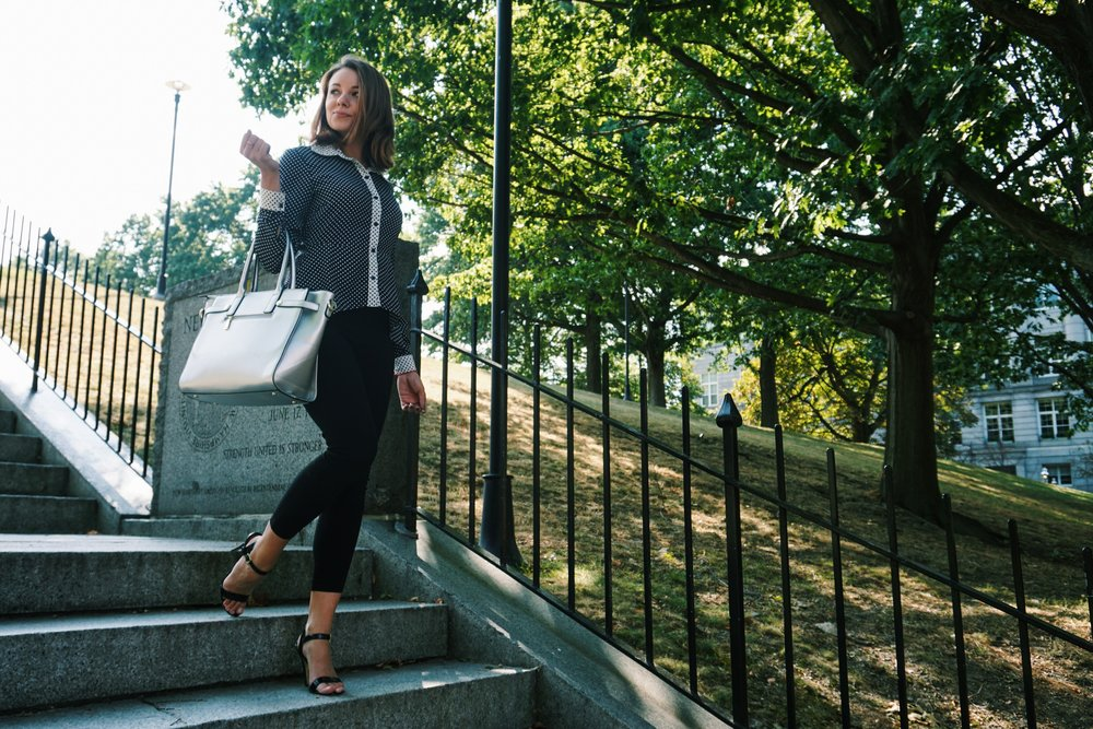 Fashion blogger walking down the stair, wearing a polka dot blouse, black capris, high heel sandals, and carrying a big silver bag.