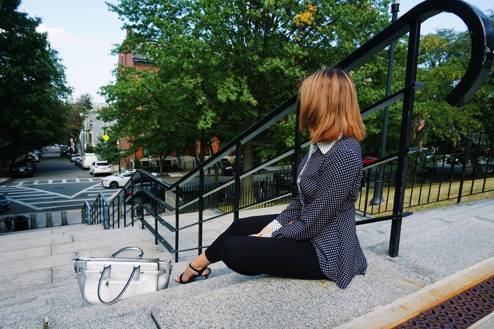 A lifestyle blogger sitting on the stairs, wearing a business casual outfit: polka dot blouse, black capris, high heeled sandals.