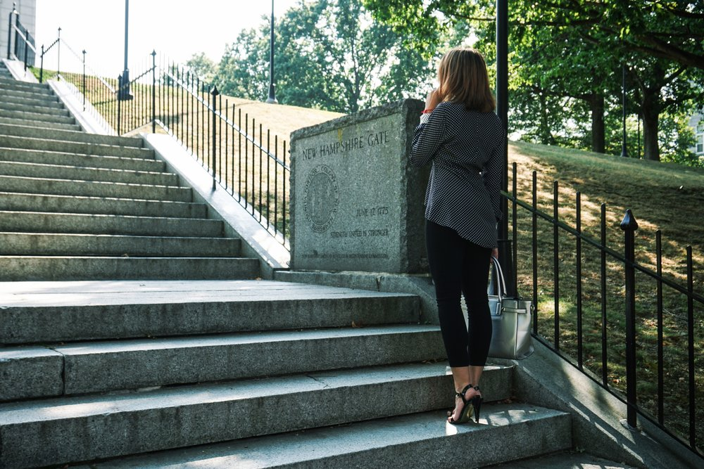 A blogger standing on the stairs, wearing a business casual/work outfit.