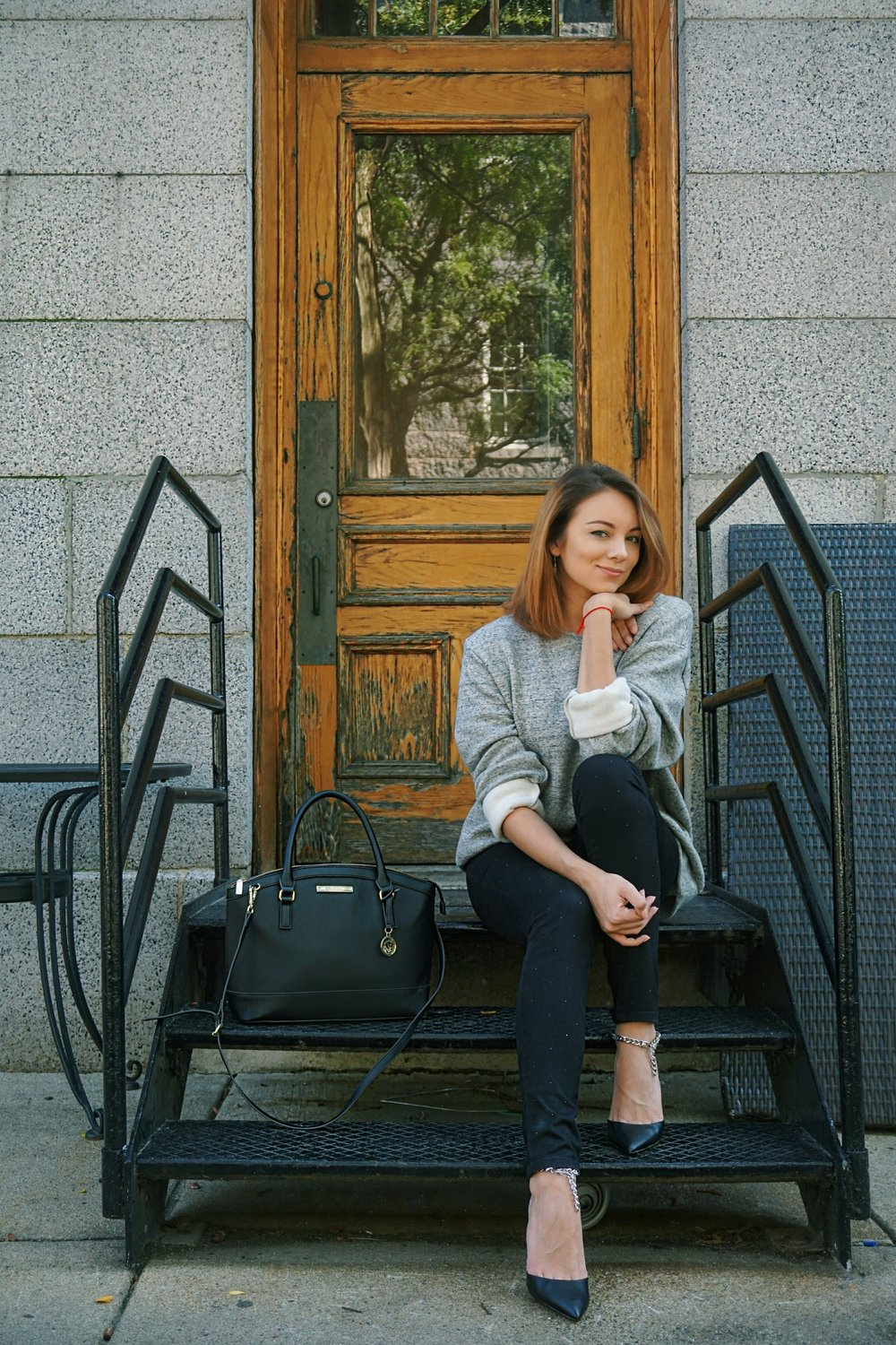 A fashion blogger sitting on the stairs wearing a men's big sweater, black Jennifer Lopez jeans, and black heels.