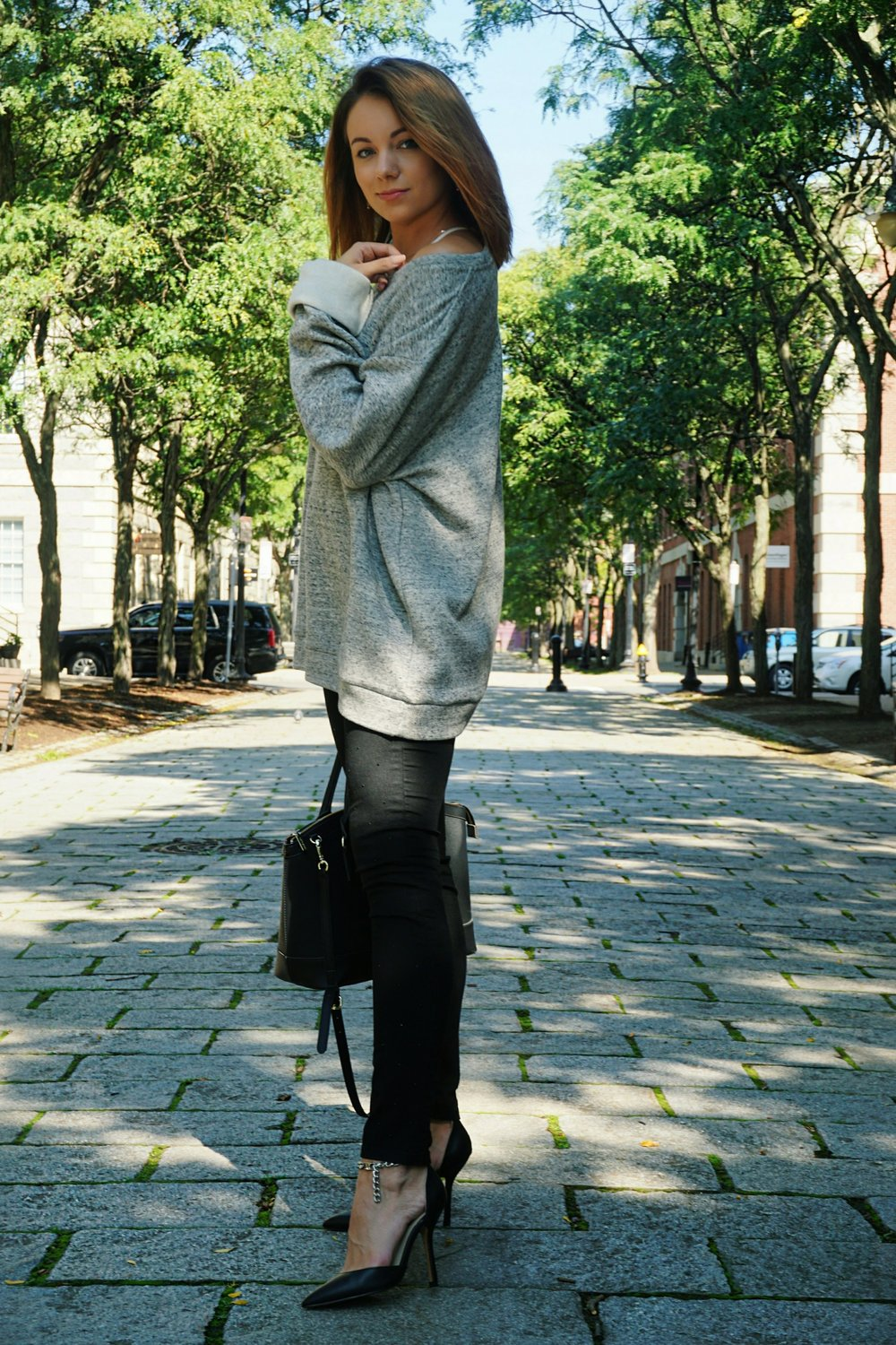 Fashion blogger wearing men's oversized gray sweater, black denim pants, black heels, and black big bag.