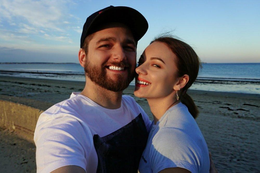 A couple smiling near the beach.