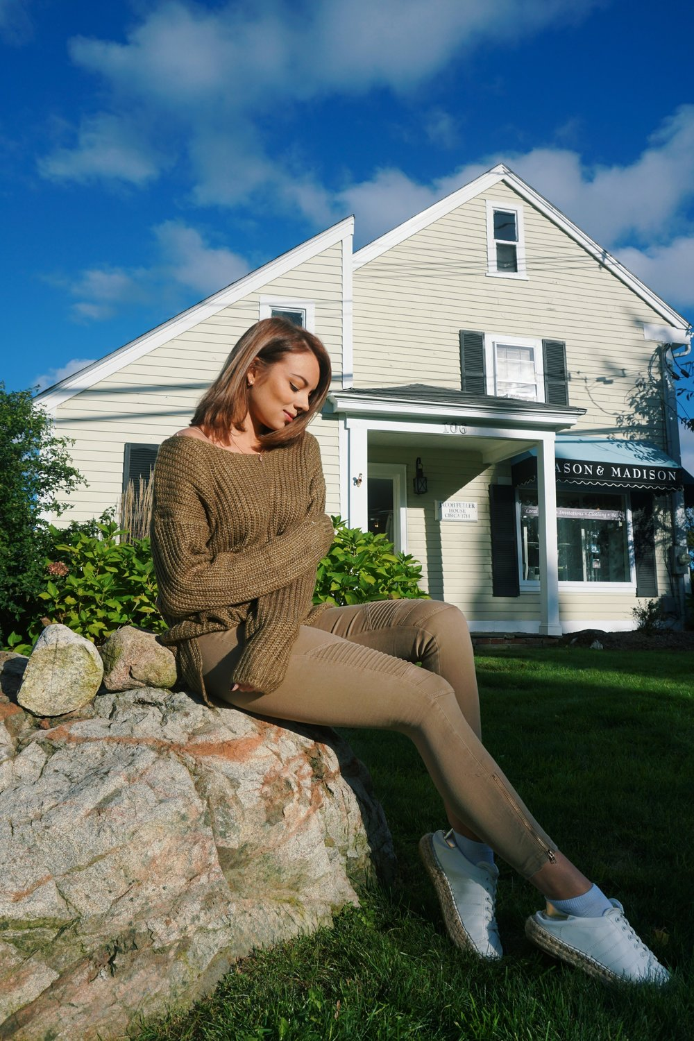 A girl sitting on a rock, wearing a cozy woven sweater, olive colour jeggings, and white sneakers.