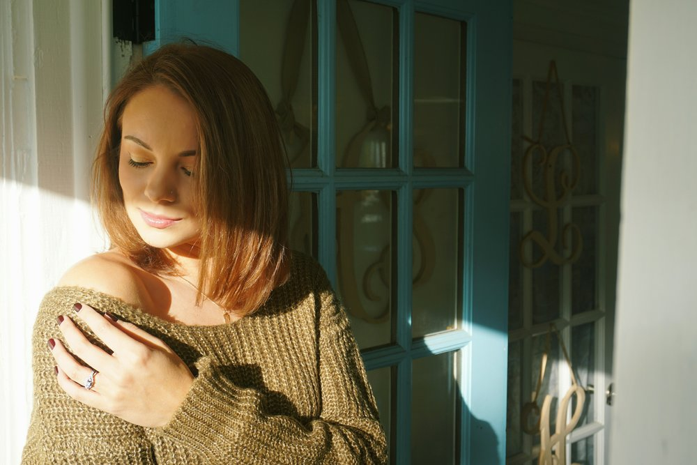 A romantic photo of a blogger. She is wearing a cozy autumn sweater.