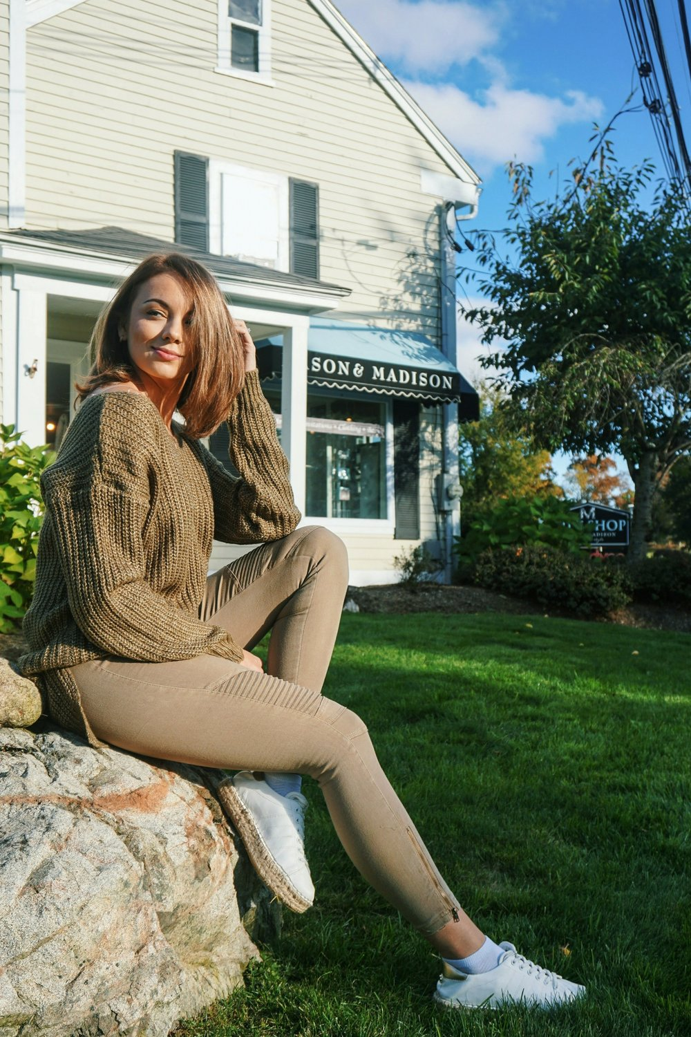 A fashion blogger sitting on a big rock wearing an autumn cozy outfit.