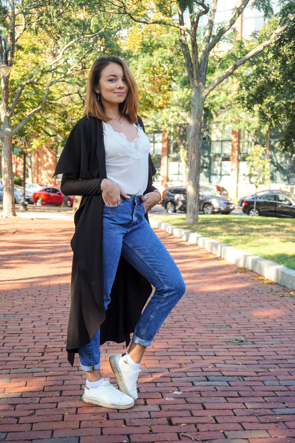 A Boston blogger wearing blue mom jeans, white top, white sneakers, and black long duster.