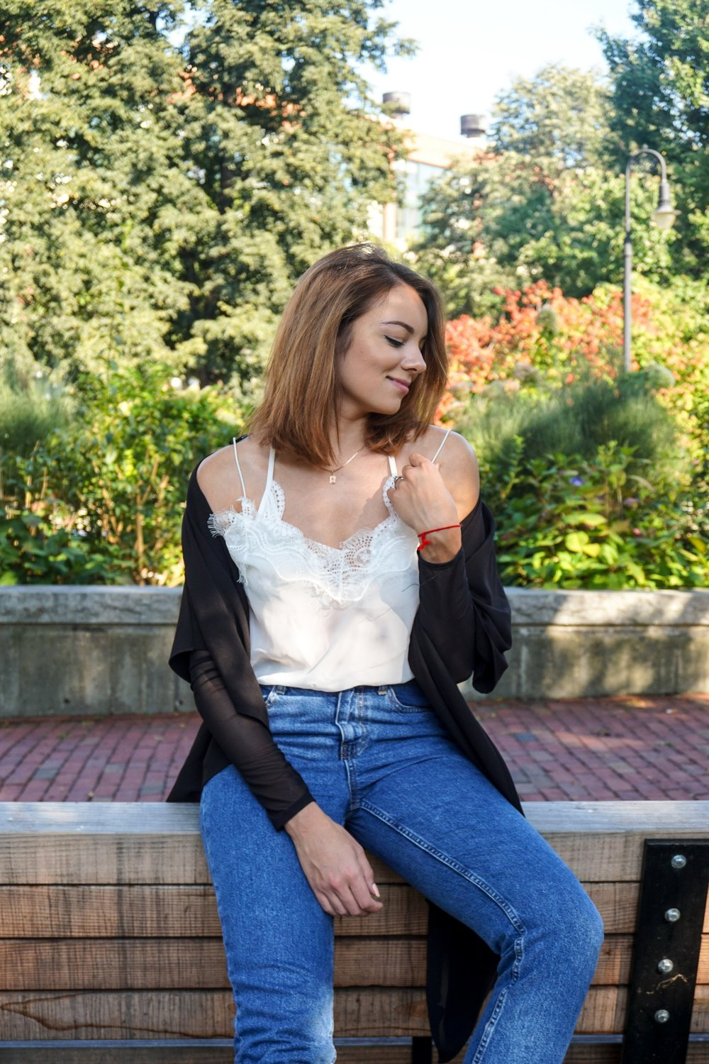 A fashion blogger wearing a white tank top with lace, blue mom jeans, and a black duster.