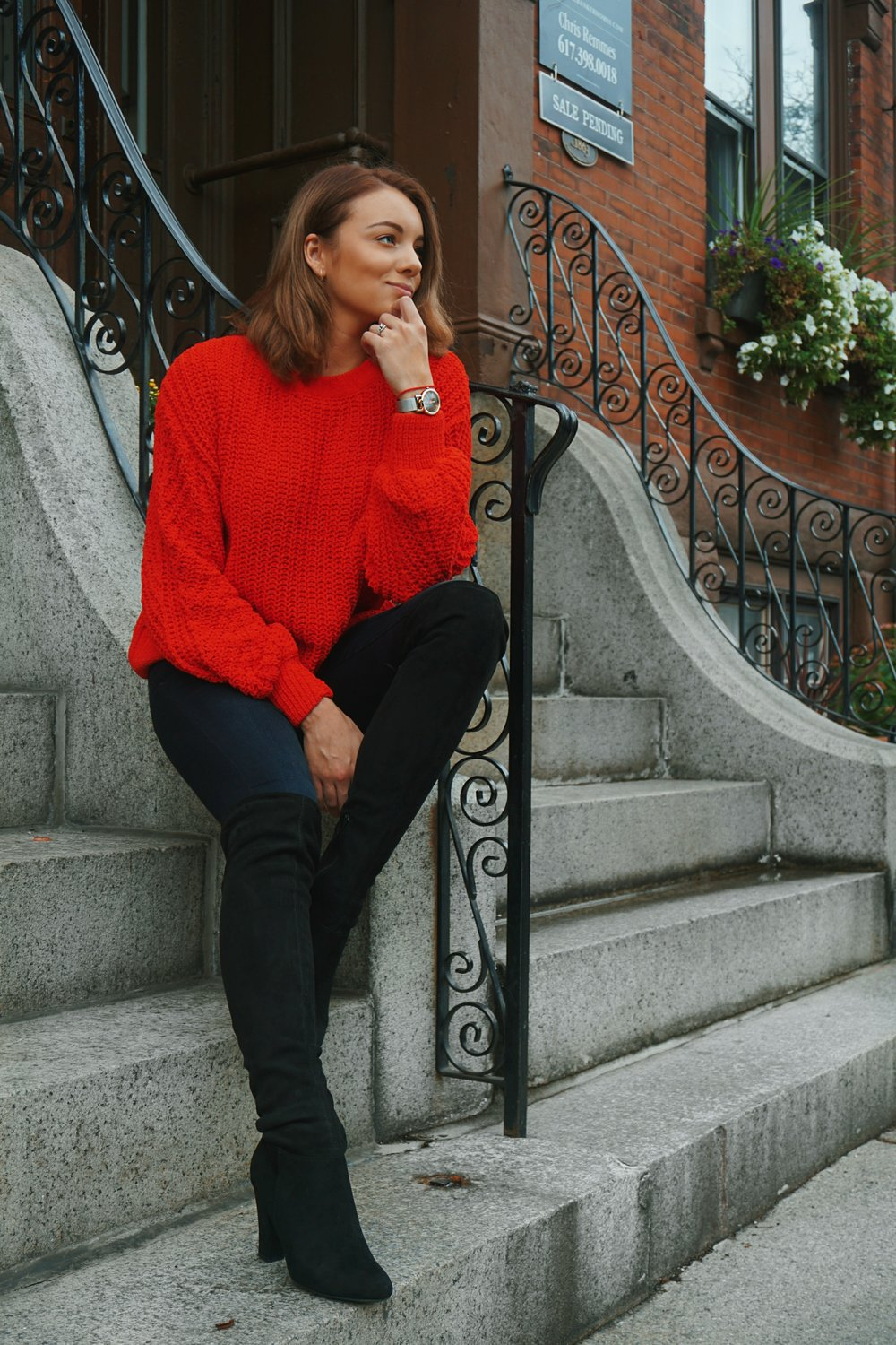 A blogger wearing a red cozy sweater, jeans, and black thigh high boots.