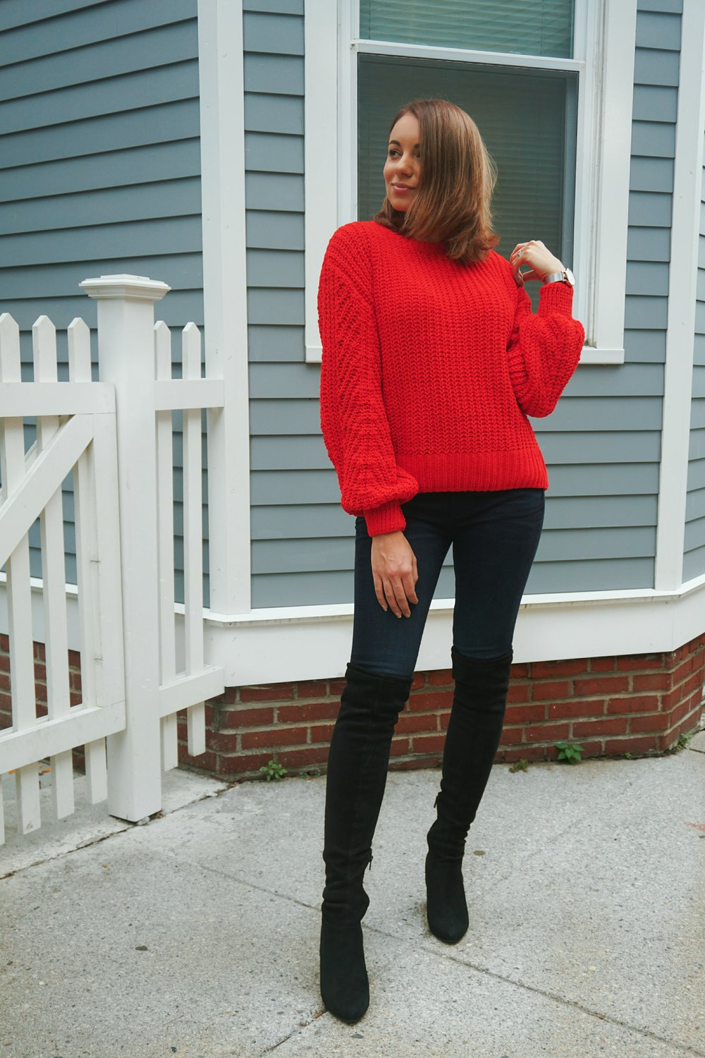 A beauty blogger wearing a sweater with bell-shaped sleeves, jeans, and thigh high boots.