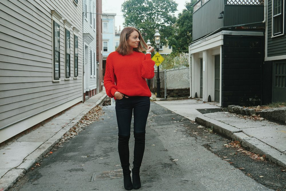 A blogger standing in the little street of Boston, wearing cozy red sweater, jeans, and thigh high boots.