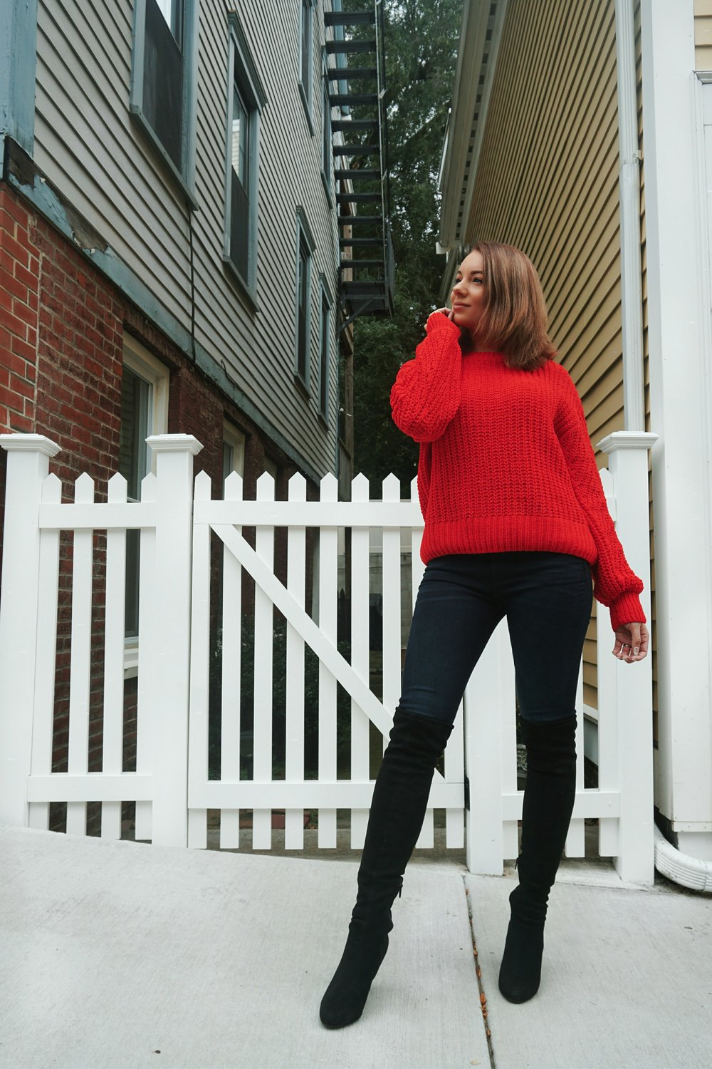 Fall outfit inspiration : red oversized sweater, jeans, and black thigh high boots.