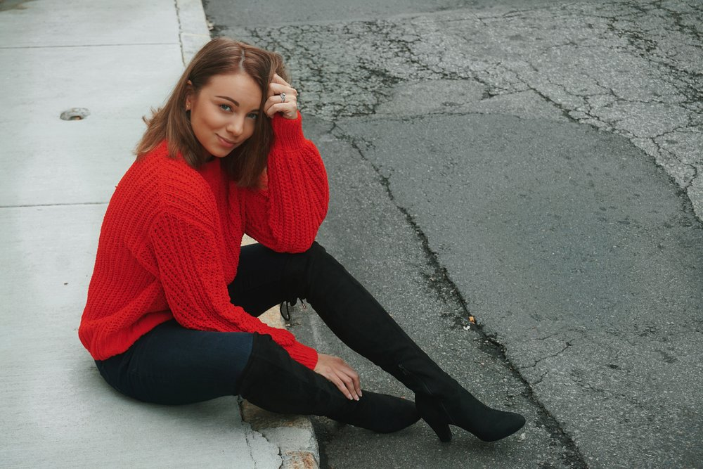 A blogger sitting on the street wearing a red h&m sweater, dark jeans, and thigh high boots.