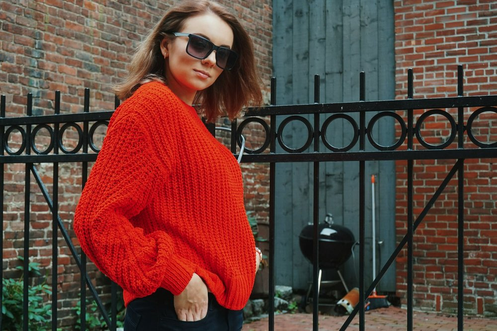 A fashion blogger wearing an h&m red sweater in front of a brick wall