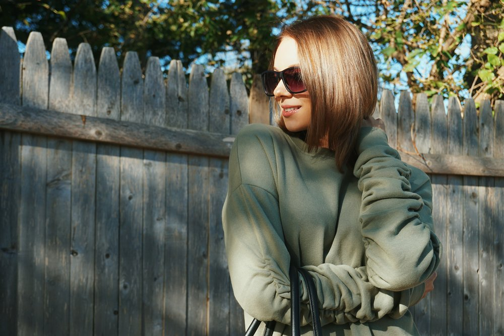 A blogger wearing a green oversized sweater.