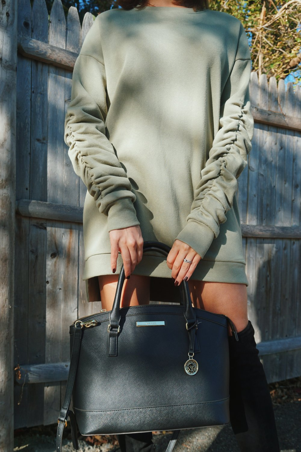 Green sweater dress, knee high boots, and a black purse.