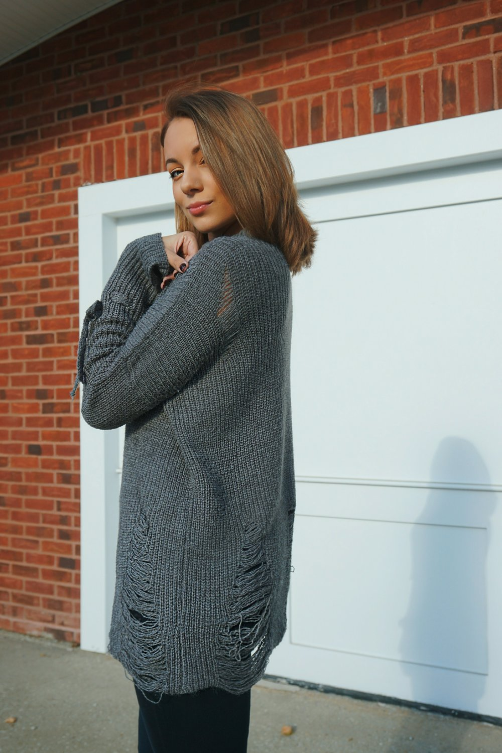 A fashion blogger wearing a gray distressed sweater.
