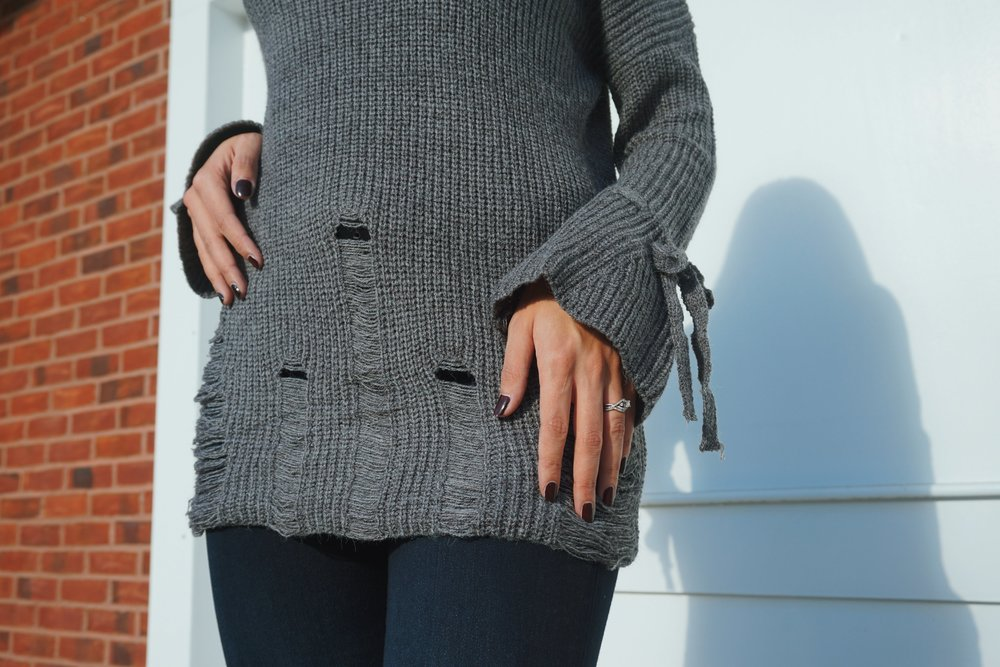 Details of a gray distressed sweater.