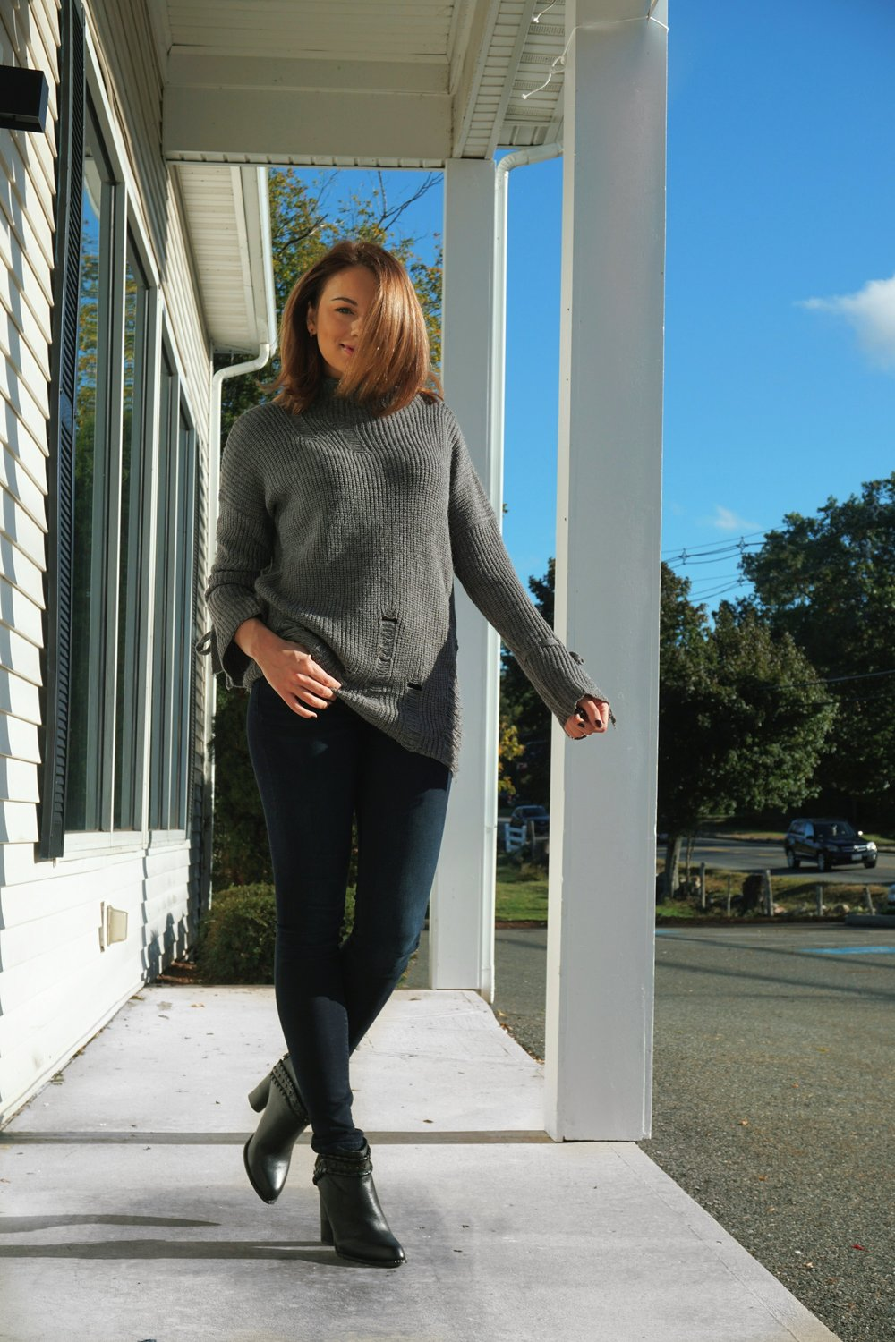 A fasion blogger wearing a gray distressed sweater, dark jeans, and high heel boots.