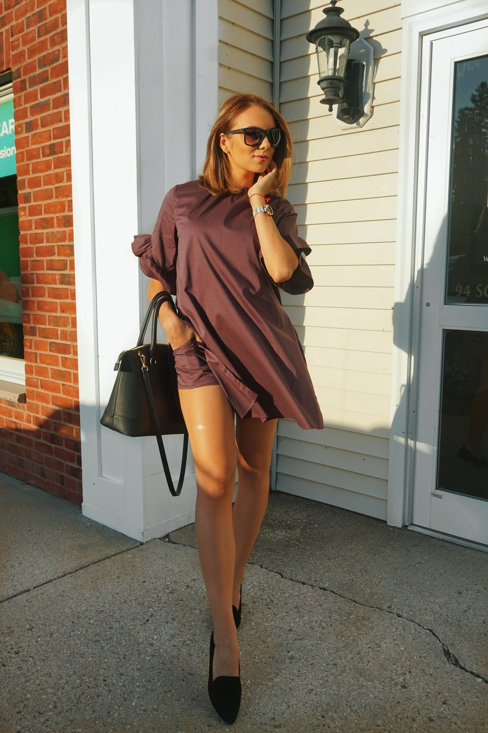 A fashion blogger wearing a plum romper dress.