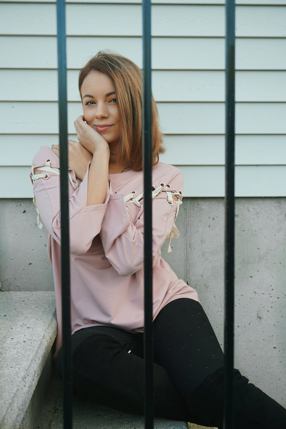 A blogger sitting on a steps, wearing a pink top, black jeans, and knee-high boots.