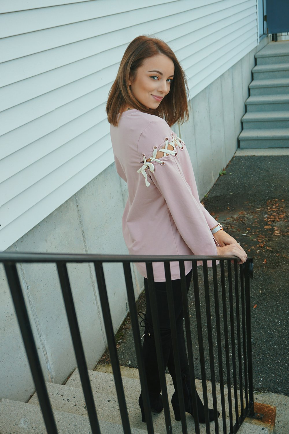 A blogger posing on the steps, wearing a pink long-sleeved top, black Jennifer Lopez jeans, and knee-high boots.