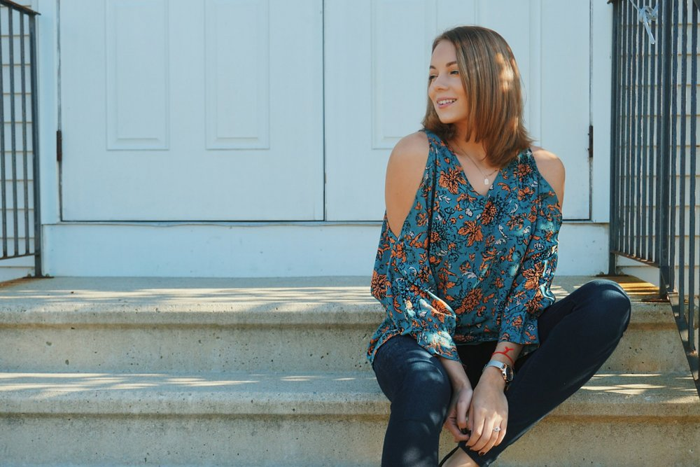 A blogger sitting on the steps, wearing a floral open-shoulder top, Express jeans, and black flats.
