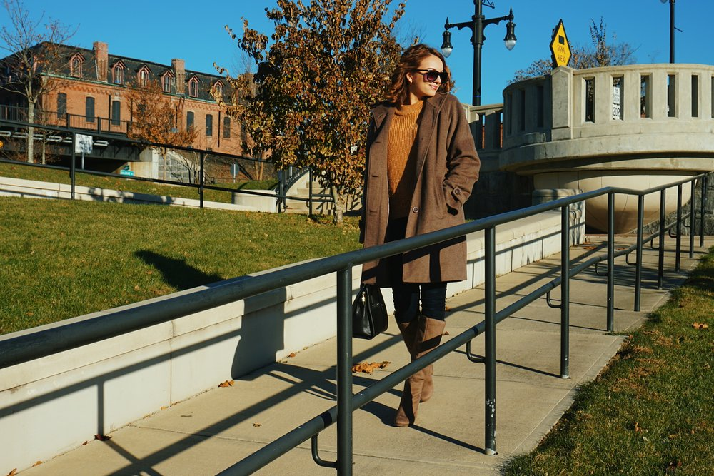 A blogger wearing a brown coat, dark blue jeans, light brown sweater, and light brown high heel boots.