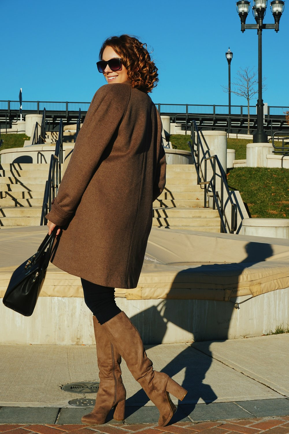 A blogger wearing an autumn outfit: brown coat, brown boots, and a black bag.