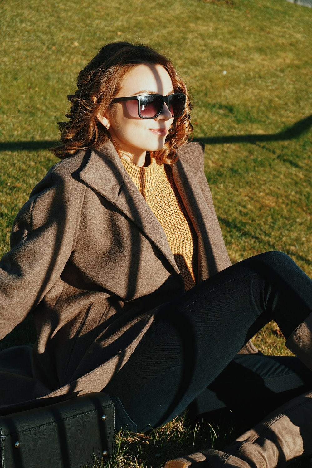A blogger sitting on the grass, wearing dark jeans, brown sweater, boots, and a black bag.