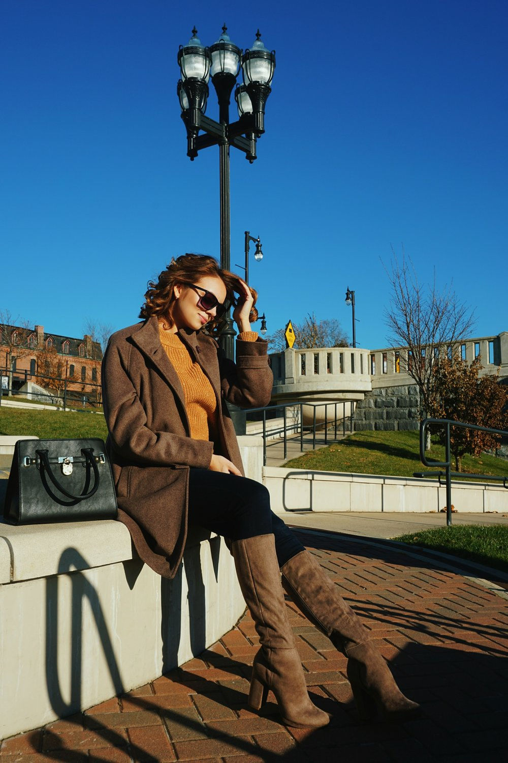 A blogger sitting on the fountain, wearing a brown coat, boots, sweater, and black purse.