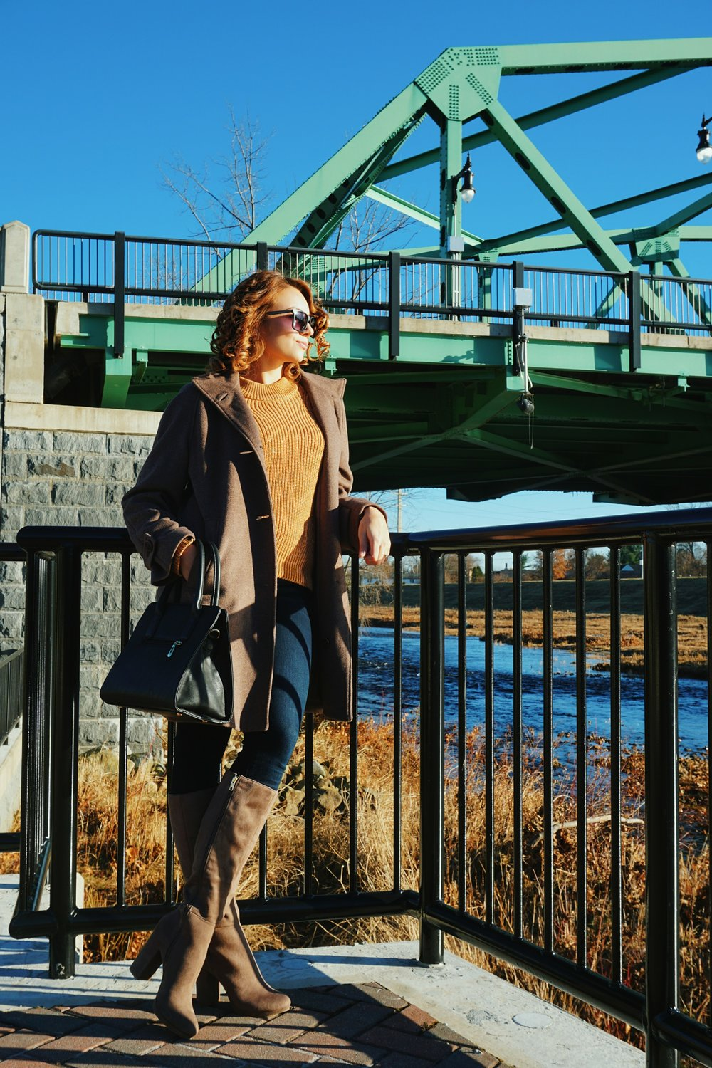 A blogger posing in front of a bridge, wearing a brown coat, high heeled boots, sweater, and a black purse.