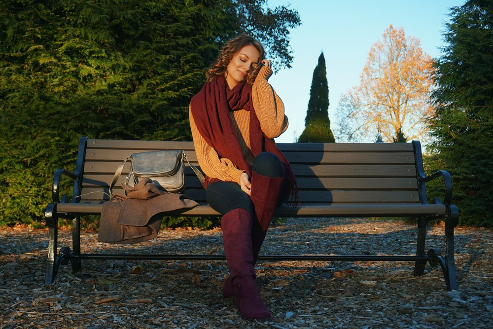 A blogger sitting on a bench, wearing a light brown sweater, maroon boots and scarf.